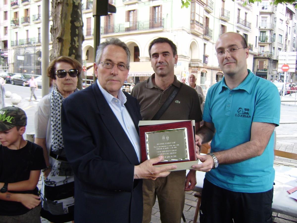 Manuel López recibiendo la placa